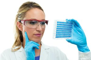 26012806 - laboratory woman examining a 96 well microplate in hand